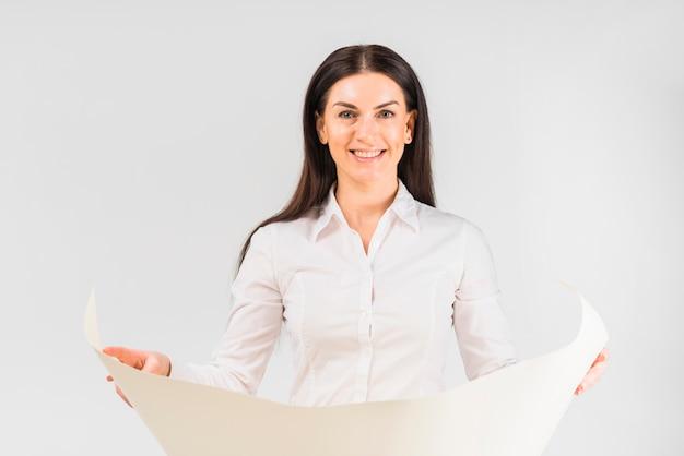 Gelukkige bedrijfsvrouw die zich met whatman-document bevindt
