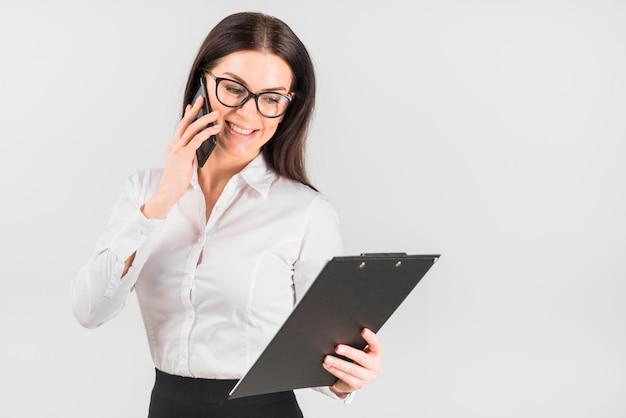 Gelukkige bedrijfsvrouw met klembord die telefonisch spreken
