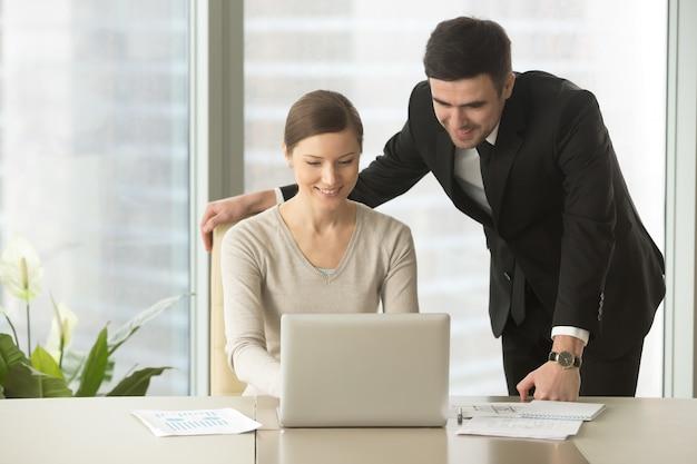 Gelukkige bedrijfswerknemers die laptop in bureau met behulp van