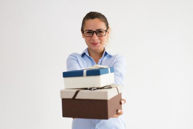 Gelukkige bedrijfvertegenwoordiger die giften aanbieden aan klanten