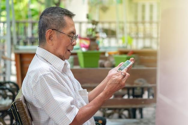 Gelukkige bejaarde aziatische oude mens die smartphone gebruiken bij openlucht.