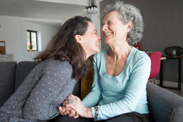 Gelukkige bejaarde en haar dochter die en handen lachen houden