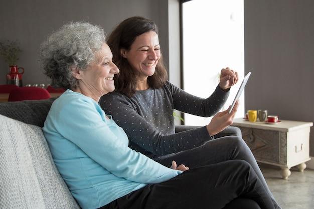 Gelukkige bejaarde en haar dochter die op tabletcomputer doorbladeren
