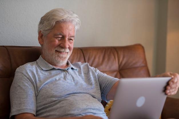 Gelukkige bejaarde man die binnen op laptop werkt en glimlacht, ontspannen senior man met behulp van computer browsen of surfen op internet, nieuws online lezen, opgewonden ouderen sms'en thuis op pc