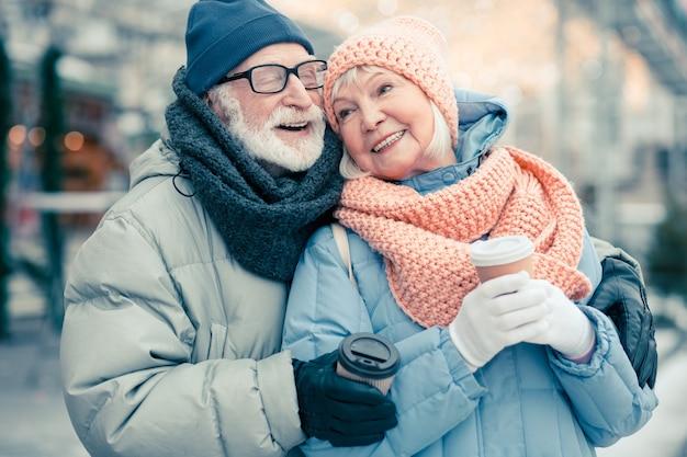 Gelukkige bejaarde man die zijn ogen sluit en glimlacht terwijl hij in de winterdag buiten is met zijn vrouw en haar knuffelt. kartonnen kopjes koffie in handen van gepensioneerden