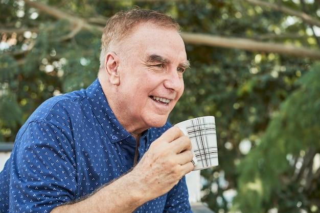 Gelukkige bejaarde man geniet van een kopje koffie in de ochtend wanneer hij op het balkon staat en wegkijkt