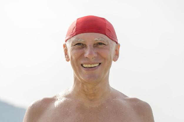 Gelukkige bejaarde man in een rode zwemhoed op het strand in de buurt van het zeewater
