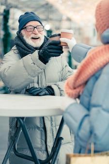 Gelukkige bejaarde man in mooie winterkleren die buiten naast de ronde straattafel staat en glimlacht terwijl hij met zijn vrouw een papieren koffiekopje klettert