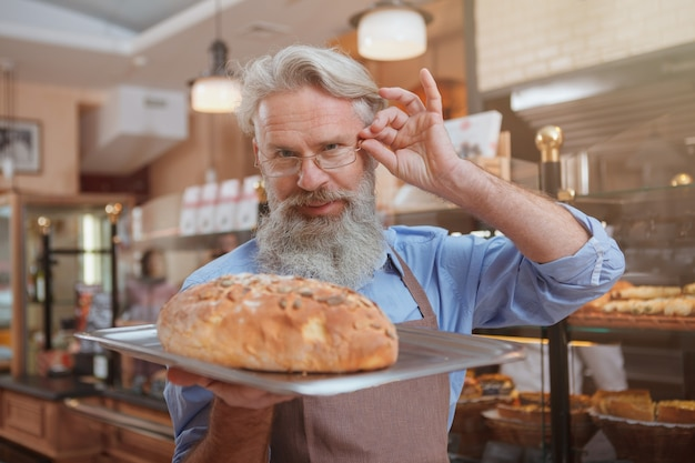 Gelukkige bejaarde mannelijke bakker die, vers gebakken brood houdt dat hij verkoopt