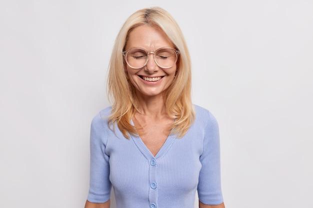 Gelukkige bejaarde vrouwelijke leraar blij om gefeliciteerd te worden met kennisdag blij om leerlingen op school te ontmoeten glimlacht vreugdevol houdt de ogen gesloten draagt grote transparante gassen blauwe trui poseert binnen