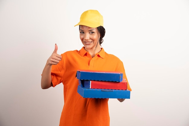 Gelukkige bezorger die pizza vasthoudt en duimen maakt