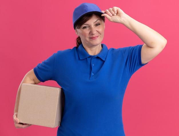 Gelukkige bezorgingsvrouw van middelbare leeftijd in blauw uniform en glb die kartondoos houden die voorzijde glimlachend zelfverzekerd over roze muur kijken