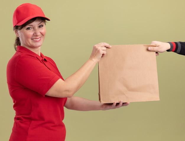 Gelukkige bezorgingsvrouw van middelbare leeftijd in rood uniform en glb die document pakket geven aan een klant die vriendschappelijke status over groene muur glimlacht