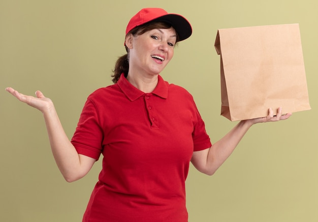 Gelukkige bezorgingsvrouw van middelbare leeftijd in rood uniform en glb die document pakket houden die voorzijde glimlachen die vrolijk voorstellen die met wapen presenteren die zich over groene muur bevinden