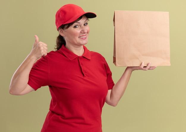 Gelukkige bezorgingsvrouw van middelbare leeftijd in rood uniform en glb die document pakket houden die voorzijde glimlachend zelfverzekerd tonen die duimen omhoog zien staan die over groene muur kijken