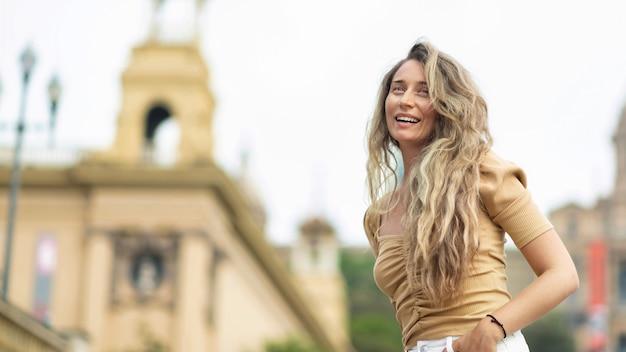 Gelukkige blanke vrouw in jurk met uitzicht op barcelona op de achtergrond, spanje