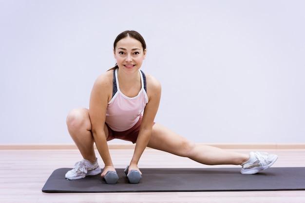 Gelukkige blanke vrouw in sportkleding beoefent yoga thuis tegen een muurachtergrond. het concept van een gezonde levensstijl en innerlijke geest. lichaamsconcentratie