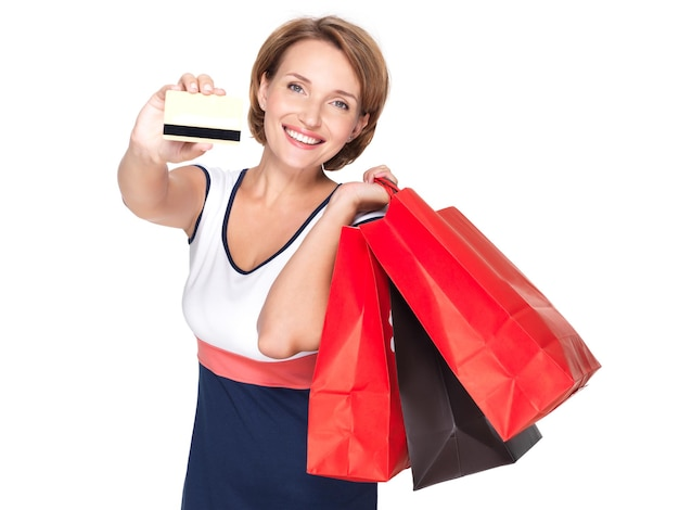 Gelukkige blanke vrouw met boodschappentassen en creditcard over witte muur