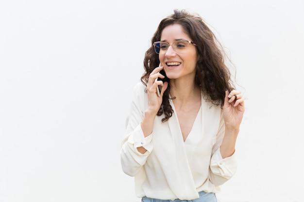Gelukkige blije vrouw die in glazen op cellphone spreekt
