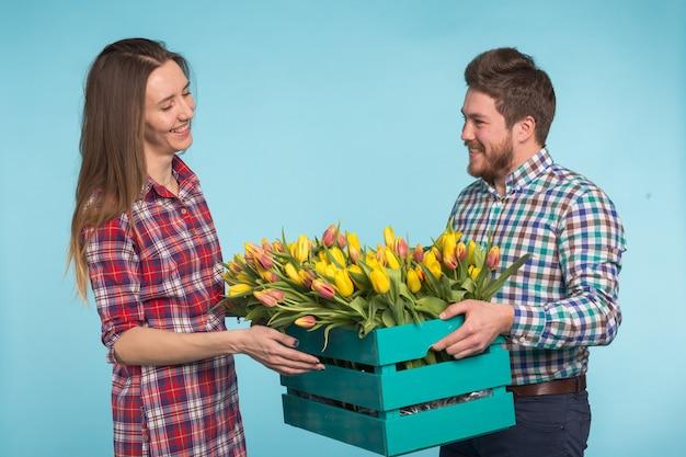 Gelukkige bloemisten die tulpen in een grote houten doos op blauw bevestigen
