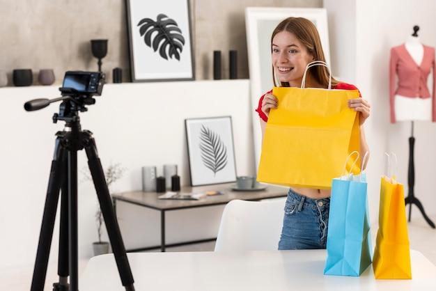 Gelukkige blogger die gele het winkelen zak houdt