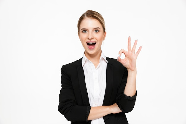 Gelukkige blonde bedrijfsvrouw die ok teken en met open mond over wit toont