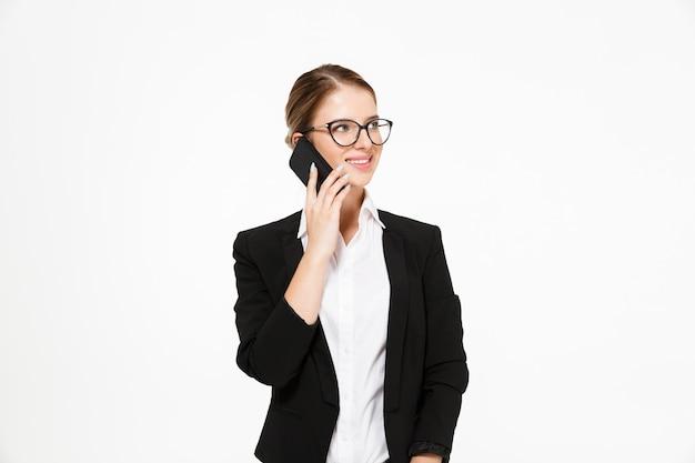 Gelukkige blonde bedrijfsvrouw in oogglazen die door de telefoon spreken en weg over wit kijken