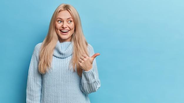 Gelukkige blonde europese vrouw heeft blije uitdrukking gekleed in gebreide trui wijst duim naar kopie ruimte