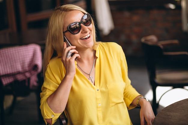 Gelukkige blonde haarvrouw die op telefoon spreekt