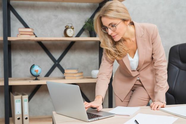 Gelukkige blonde jonge onderneemster die op laptop op het werk in het bureau typen
