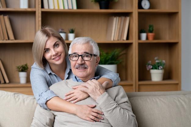 Gelukkige blonde jonge vrouw die haar vrolijke hogere vader op bank omhelst terwijl beiden naar u kijken tijdens thuis ontspannen
