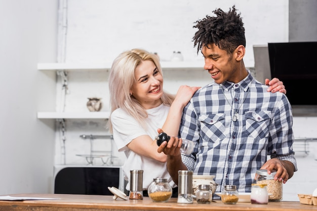Gelukkige blonde jonge vrouw die zich achter haar vriend bevindt die het voedsel in de keuken voorbereidt
