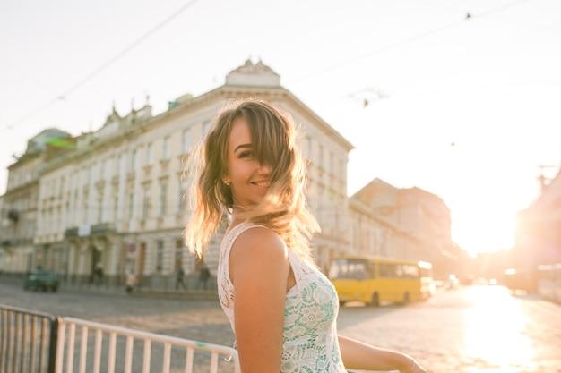 Gelukkige blonde jonge vrouw met charmante glimlach die zich voordeed bij de zonsopgang en de schittering van de zon