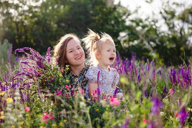 Gelukkige blonde moeder en dochter in een zomerbloeiend veld met een boeket wilde bloemen in hun handen
