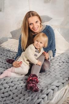 Gelukkige blonde moeder omhelst haar kleine babydochter op het grote bed in de winter. familie bij gezellig huis.