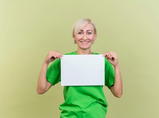 Gelukkige blonde slavische vrouw op middelbare leeftijd die leeg document houdt dat op olijfgroene muur wordt geïsoleerd