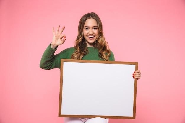 Gelukkige blonde vrouw die een leeg bord vasthoudt en een goed teken toont terwijl ze naar de voorkant over de roze muur kijkt