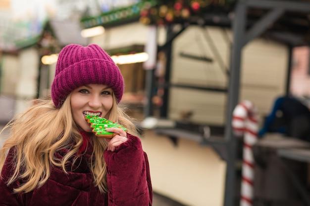 Gelukkige blonde vrouw die heerlijke kerstkoekjes eet op straat in kiev