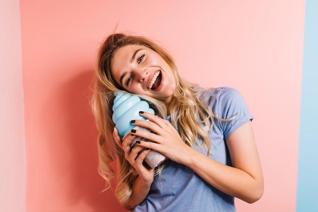 Gelukkige blonde vrouw die op roze muur lacht