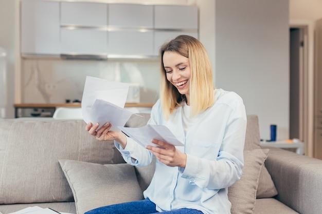 Gelukkige blonde vrouw die thuis op de bank zit, blij met tijdige betaling van kredietrekeningen en het sluiten van de kredietlijn, ontving goed nieuws van de bank