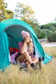 Gelukkige blonde vrouw in hoed die thee drinkt, in tent zit en weg kijkt. kaukasische langharige reiziger kamperen op gazon in park en ontspannen op de natuur. toerisme, avontuur en zomervakantie concept