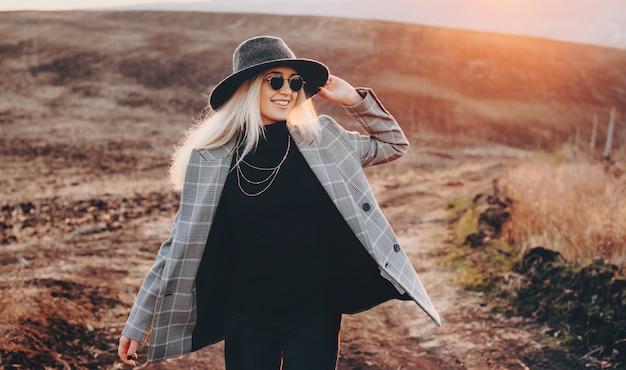 Gelukkige blonde vrouw met bril en hoed die een grijze jas loopt en in een veld glimlacht