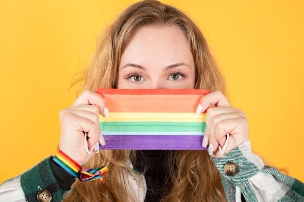 Gelukkige blonde vrouw met gay pride-vlag, masker, holebi-vrij liefdeconcept, gele achtergrondexemplaarruimte
