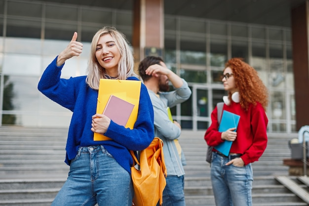 Gelukkige blonde vrouw met notitieboekjes dichtbij klasgenoten