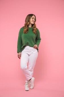 Gelukkige blonde vrouw van volledige lengte, gekleed in een groene trui die poseert en wegkijkt over roze muur
