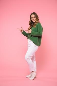 Gelukkige blonde vrouw van volledige lengte, gekleed in een groene trui die wegwijst en naar de voorkant kijkt over de roze muur