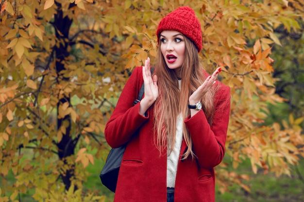 Gelukkige blondevrouw in rode hoed en jasje het stellen in de herfstpark.