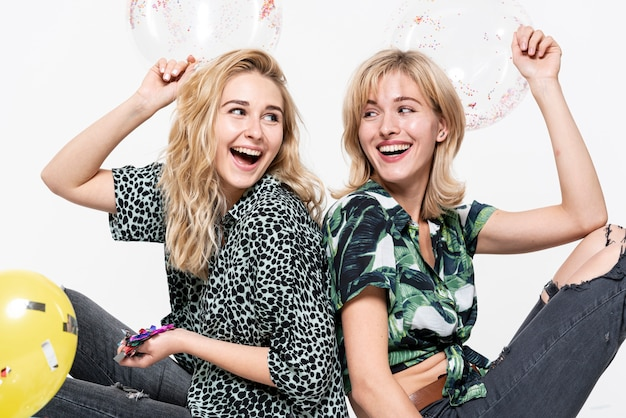 Gelukkige blondevrouwen die confettien houden