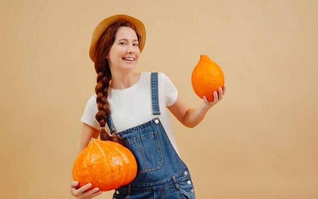 Gelukkige boerenvrouw in een denim jumpsuit houdt rijp pompoenen herfstoogst concept van landbouw