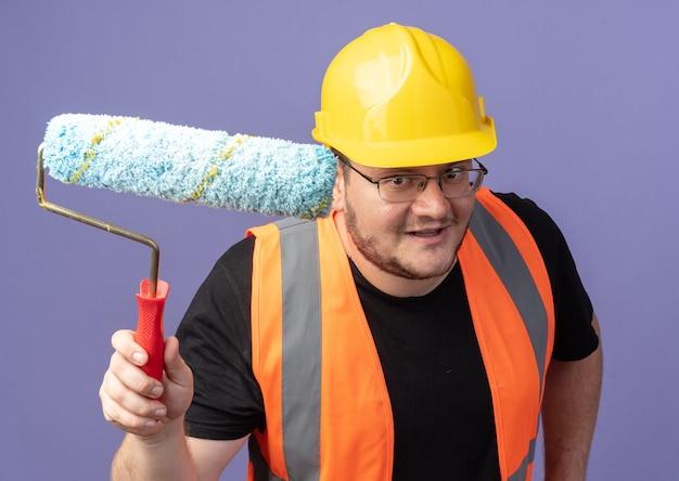 Gelukkige bouwman in bouwvest en veiligheidshelm die een verfroller vasthoudt en naar een camera kijkt die vrolijk over blauw staat te glimlachen